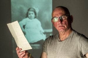 Actor Gary Lewis with Robert Climie's letter detailing his opposition to WW1, written to his daughter Cathie who is pictured in the background Photograph Peter Devlin