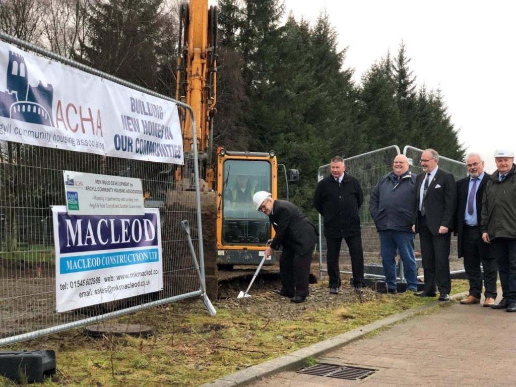 Councillor Donnie MacMillan BEM accompanied by Oban councillors Roddy McCuish, Jim Lynch, and Douglas Prophet from ACHA's governing body, ACHA chief executive, Alastair MacGregor, and Kenny MacLeod of MacLeod Construction. NO_T04_Kilmartin Sod Cut