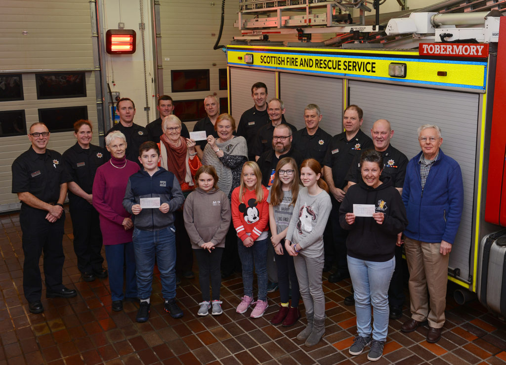 Pictured are Firefighters from Tobermory Fire Station presenting cheques to various Mull Community groups. The money (£600) was raised at the Fire Stations open day, manned by Firefighters from Tobermory and Salen Fire Stations. A further £600 was raised for The Fire Fighters Charity. NO_T04_TobermoryFireStation01_By-AJ-Macleod