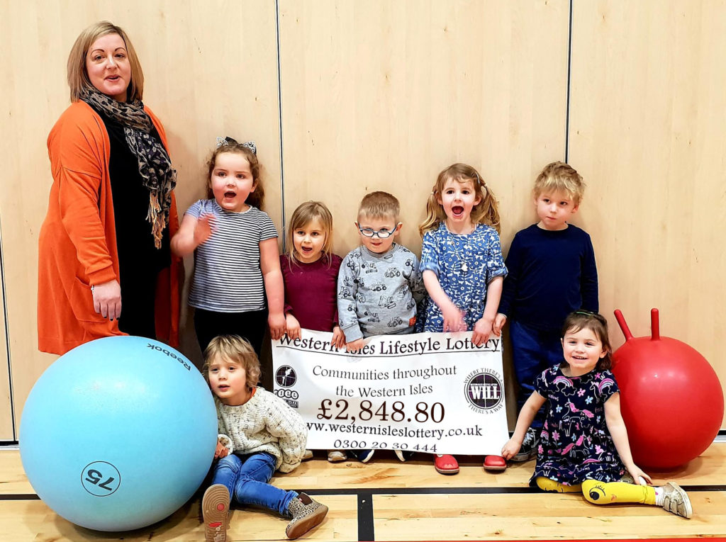 Pictured are delighted children in North Uist with Rhoda Maclennan-Trusswell of Claddach Kirkibost Centre receiving a cheque for £2,848. NO_T06_Uist01