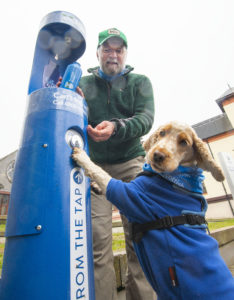 Mountaineer and Adventurer Cameron McNeish gets a little help from Millie, the Scottish Water Cocker Spaniel as he fills up his water bottle from the new tap installed at the end of the West Highland Way in Fort William. PICTURE IAIN FERGUSON, THE WRITE IMAGE. NO F13 WEST HIGHLAND WAY WATER TAP 01