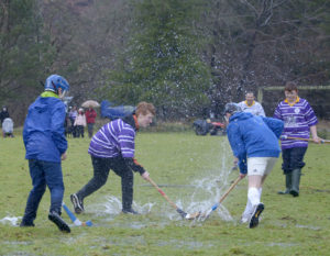 The pitch conditions make the match a bit more of a challenge for these young players. Photograph: Iain Ferguson, alba.photos NO F 03 Shinty weather