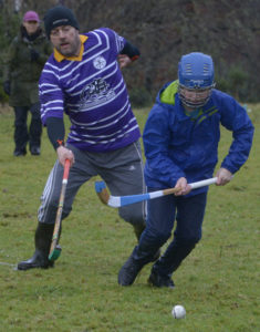 Iain MacFarlane on the left is clearly handicapped by his wellies as he is rounded by an opposing player in the traditional New Year Glenfinnan Shinty match. Photograph: Iain Ferguson, alba.photos NO F03 Glenfinnan shinty 04