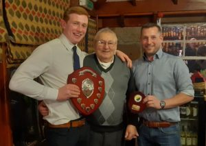 Nick Dalgety, left, holding the shield with Alan MacDonald centre and Glengarry's chairperson Scott Bremner right looking on. NO F03 Glengarry shinty 02