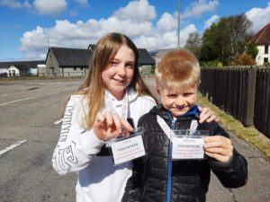 Two of the group's younger volunteers, Lucy and Angus Riddle, display their official badges. NO-F19-Caol-support-young-volunteers.jpg