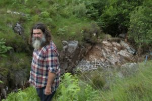 John Bryden beside the gouged out hillside. PICTURE IAIN FERGUSON, THE WRITE IMAGE. NO F27 FLASH FLOOD HIT CHARITY 02