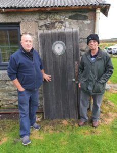 Michael and David Martin with one of the doors salvaged from the SS Aska, the ship on which their uncle, John Martin, died in 1940.