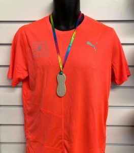 The T-shirt and medal that adult participants will receive.