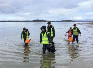 The pupils are enjoying exploring the beach near their school.