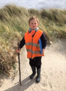 Lochlen Gibbs walking like an explorer with a stick he found on the beach – the school's very own John Muir.
