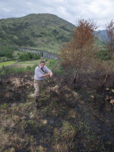 Glenfinnan Estate manager Alistair Gibson examines the destruction caused by the recent wild fire on the hillside above the famous Glenfinnan Viaduct, seen in the background. Photograph: Iain Ferguson, alba.photos NO F24 Glenfinnan fires 02