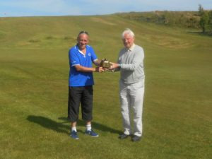 Last year's winner Sandy Watson, right, presenting Neil Brodie with the trophy.