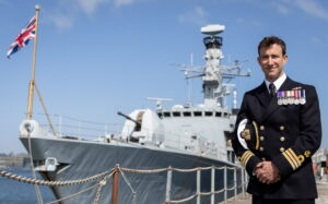 Commander Charlie Wheen in front of HMS Argyll. Photograph: Royal Navy.