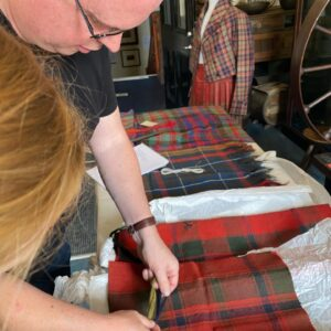 Watched by Nikki Laird, Robin Elliott examines the piece of iconic tartan. Photograph: Courtesy of Jo Watson and by permission of West Highland Museum. NO F28 Flora tartan 02