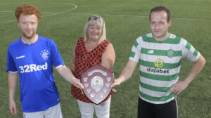 Hopeful skippers Rangers' Sam Moffat and Celtic's Michael MacLean with Lesley MacDougall, who presented it to Michael after his teams' 6-2 win. Photograph: Iain Ferguson, alba.photos NO F29 Island Park captains